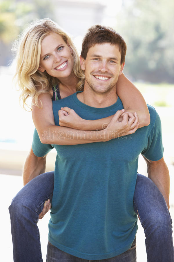 Download Young Man Giving Woman Piggyback Outdoors Stock Photo - Image: 11502806