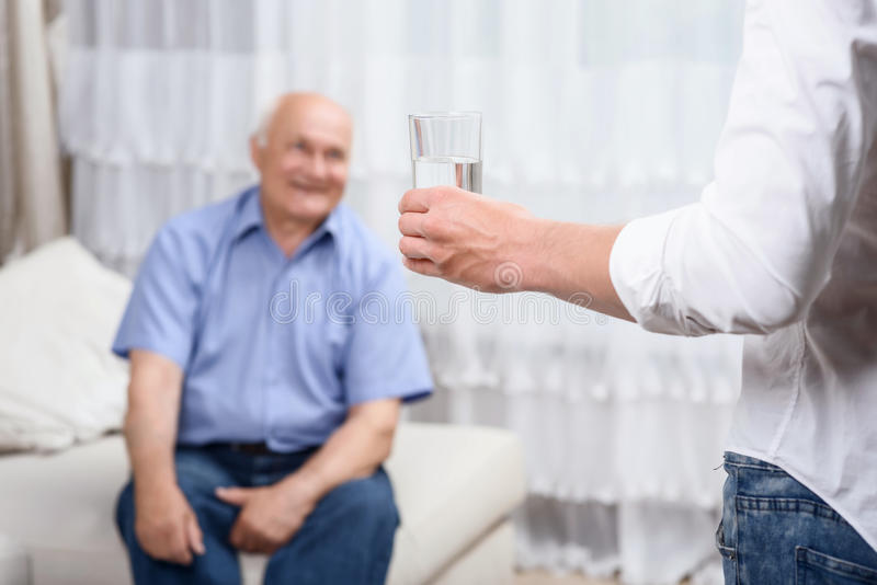 Young man with glass of water near grandfather stock images