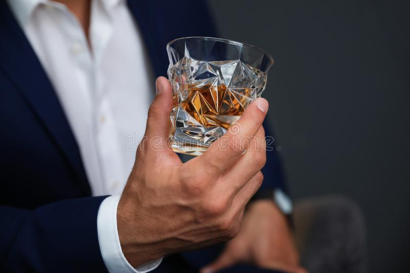 Young man with  of whiskey on dark background, closeup view. Young man with glass of whiskey on dark background, closeup view stock photography