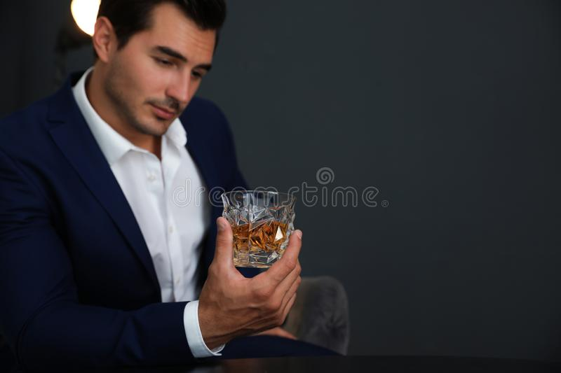 Young man with glass of  on dark background. Space for text. Young man with glass of whiskey on dark background. Space for text stock photos