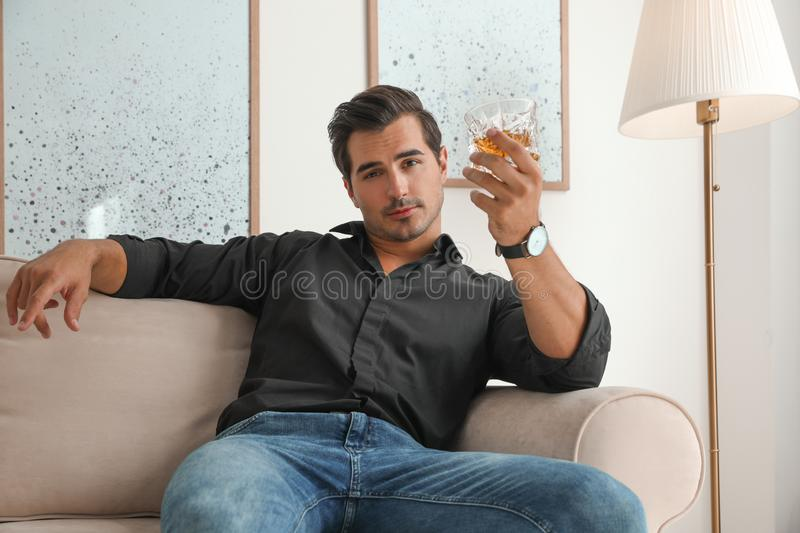 Young man with glass of whiskey. At home royalty free stock photos