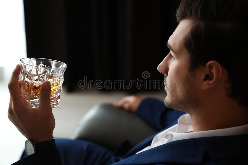 Young man with glass of whiskey. Indoors stock images