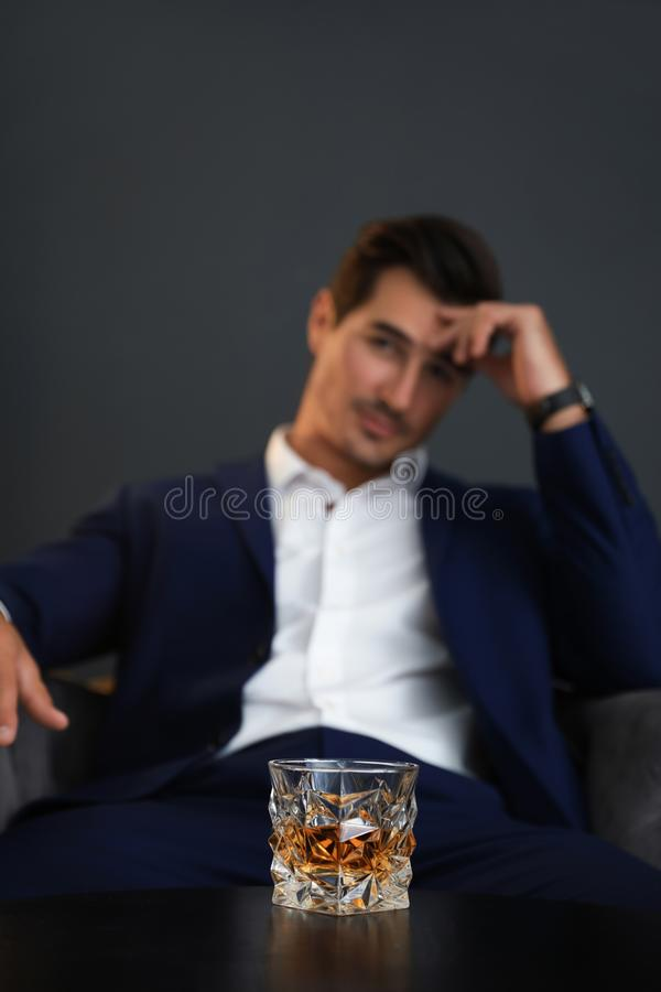 Young man with glass of  indoors. Young man with glass of whiskey indoors royalty free stock image