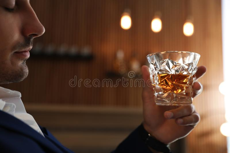 Young man with glass of  indoors, closeup. Young man with glass of whiskey indoors, closeup stock images