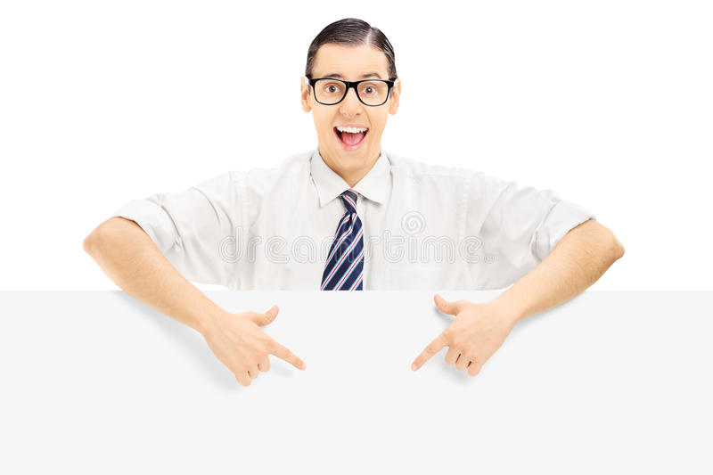 Young man with glasses pointing on a blank panel with both hands stock photography