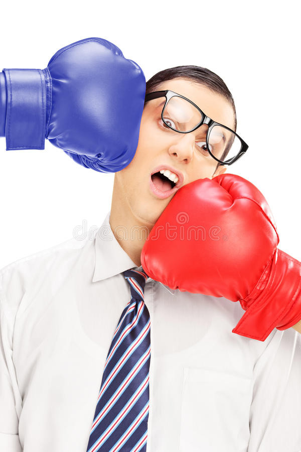 Young man with glasses punched by two boxing gloves royalty free stock photography
