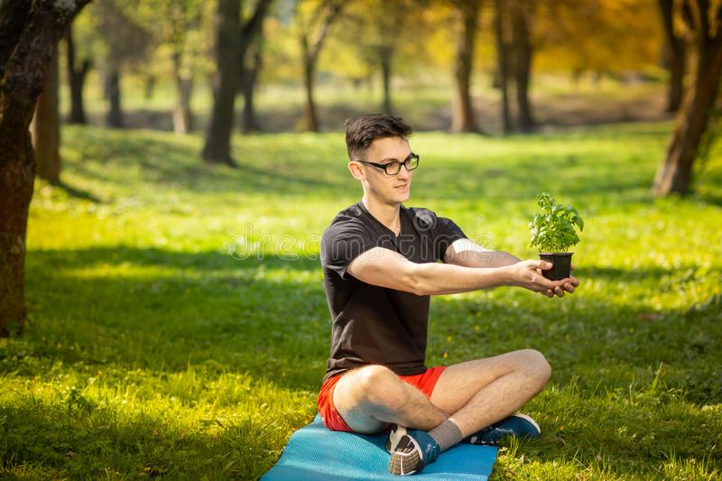 Young man in glasses resting in a park on a blue mat, holds fresh basil in hand on green background. Health lifestyle.  royalty free stock images