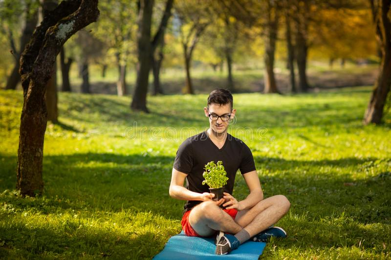 Young man in glasses resting in a park on a blue mat, holds fresh basil in hand on green background. Health lifestyle.  stock photography
