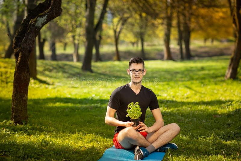 Young man in glasses resting in a park on a blue mat, holds fresh basil in hand on green background. Health lifestyle.  royalty free stock image