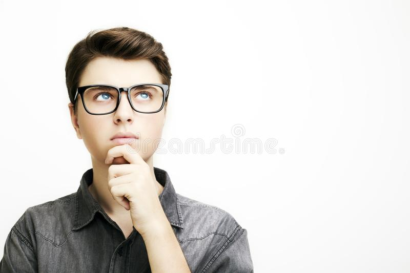 Young man with glasses is thinking on white background. stock photo