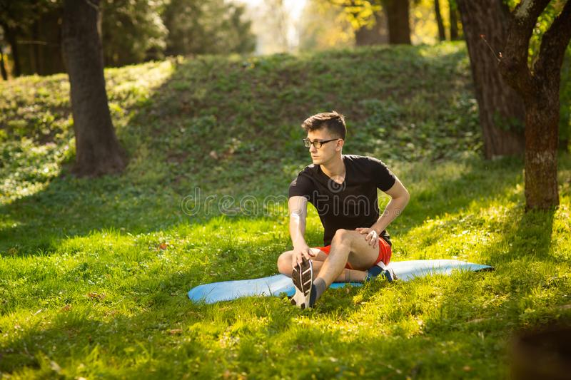 Young man in glasses training yoga outdoors. Sporty guy makes relaxing exercise on a blue yoga mat, in park. Copy space stock images