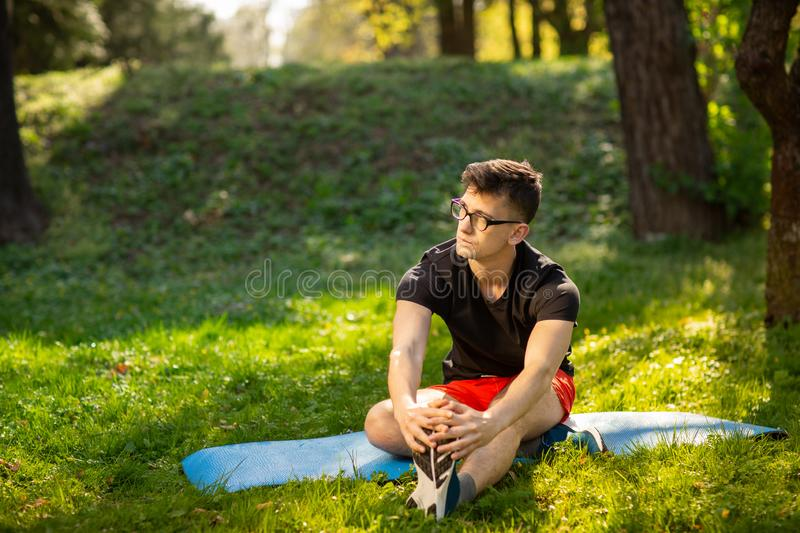 Young man in glasses training yoga outdoors. Sporty guy makes relaxing exercise on a blue yoga mat, in park. Copy space stock photography