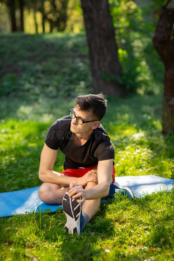 Young man in glasses training yoga outdoors. Sporty guy makes relaxing exercise on a blue yoga mat, in park. Copy space royalty free stock images