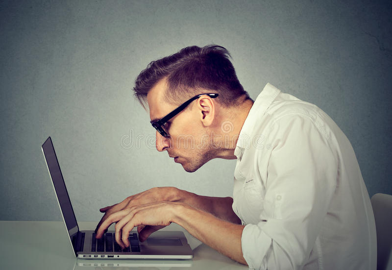 Young man in glasses working on computer sitting at desk royalty free stock photography