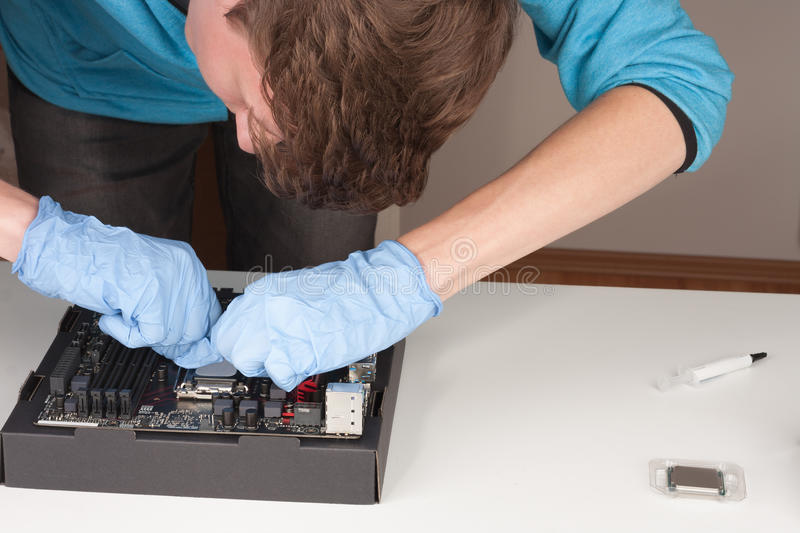 Young man with gloves openning slot for CPU on motherboard. stock photo
