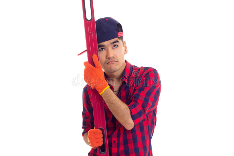 Young man in gloves and snapback holding level royalty free stock photo