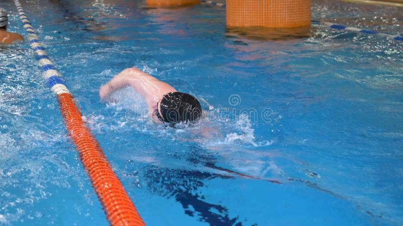 Young man with goggles and cap swimming in the blue water of swimming pool, indoor. Sportsman swims in clear water of stock photos