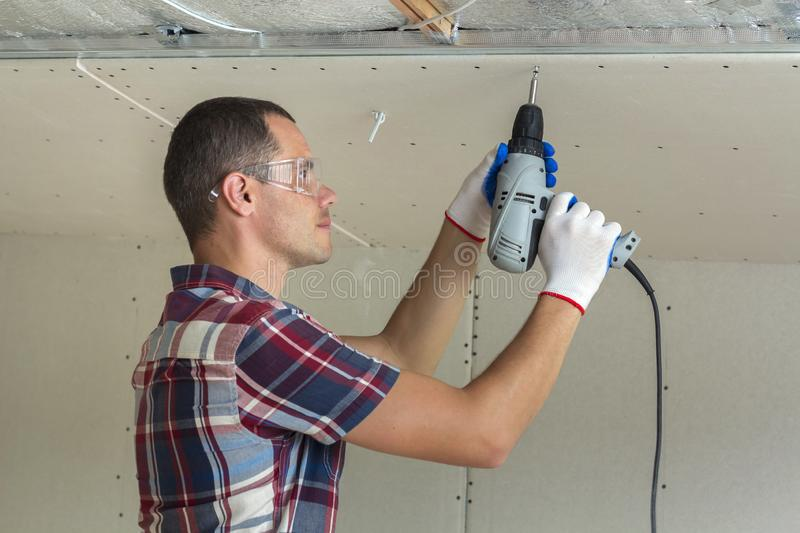 Young man in goggles fixing drywall suspended ceiling to metal f stock photo
