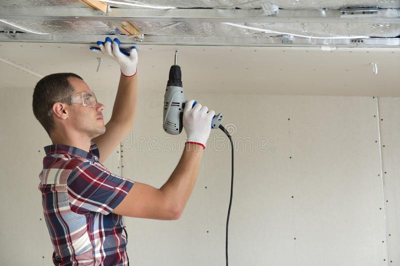 Young man in goggles fixing drywall suspended ceiling to metal frame using electrical screwdriver on ceiling insulated with shiny stock photos