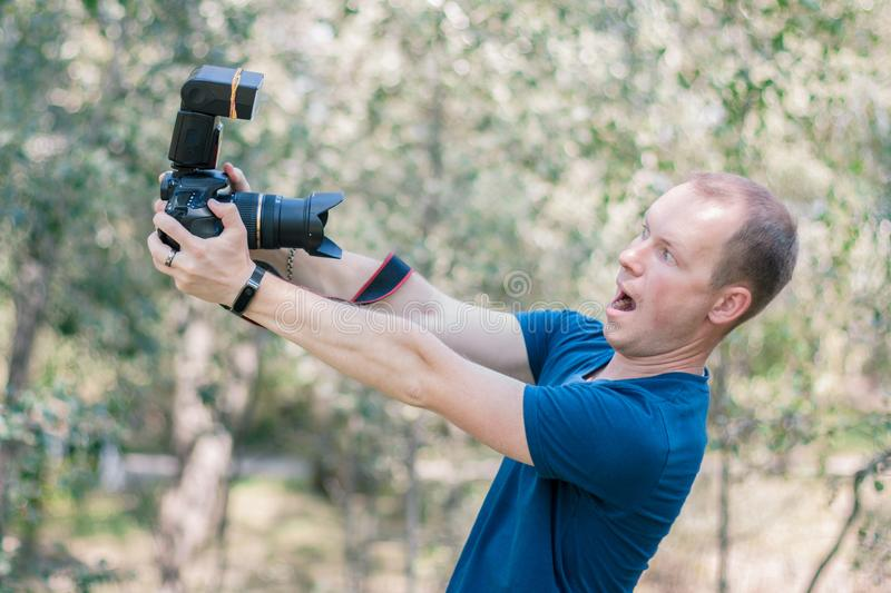 Young male guy got scared of the DSLR camera holding it in his hands on summer day. Funny picture of beginners in career of photog stock images
