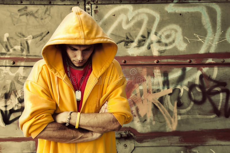 Young man on graffiti grunge wall. Young man portrait in hooded sweatshirt / jumper on grunge graffiti wall royalty free stock photos
