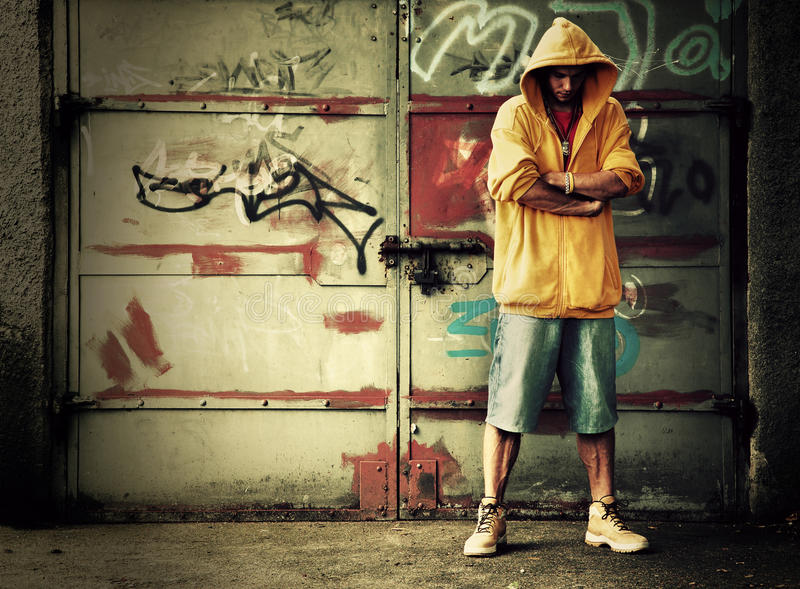Young man on graffiti grunge wall. Young man portrait in hooded sweatshirt / jumper on grunge graffiti wall royalty free stock images