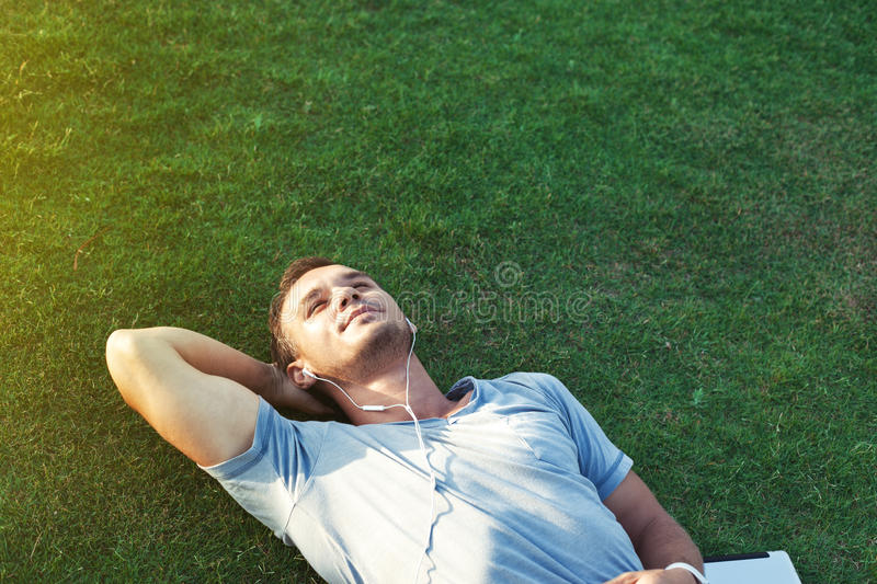 Young man on the grass listening music stock photo