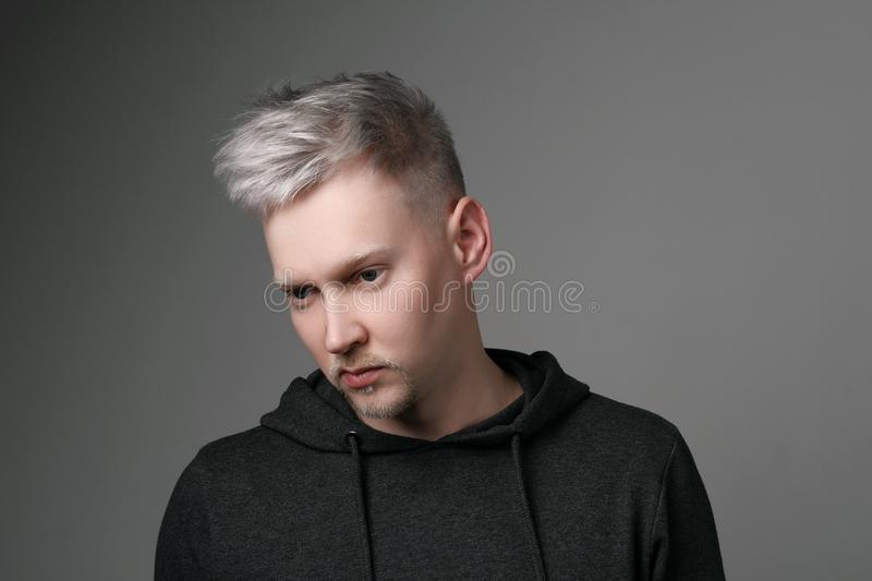 Young man with gray hair in casual clothes on white and gray background. Portrait in the studio. Creative hair coloring. royalty free stock photo
