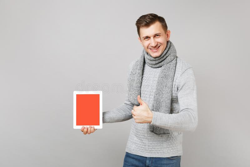 Young man in gray sweater, scarf showing thumb up, holding tablet pc computer with blank empty screen isolated on grey stock photography