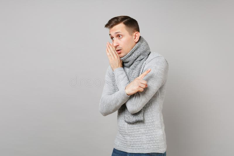 Young man in gray sweater, scarf whispers gossip, tells secret with hand gesture, point index finger aside on royalty free stock images