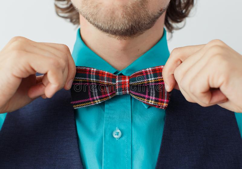 Young man in green shirt with beard in a bowtie stock photos