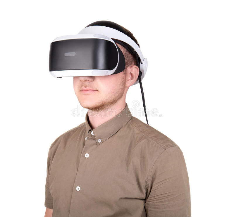 Young man in a green shirt wearing virtual reality glasses, isolated on white background. New and professional audio equipment. royalty free stock photography