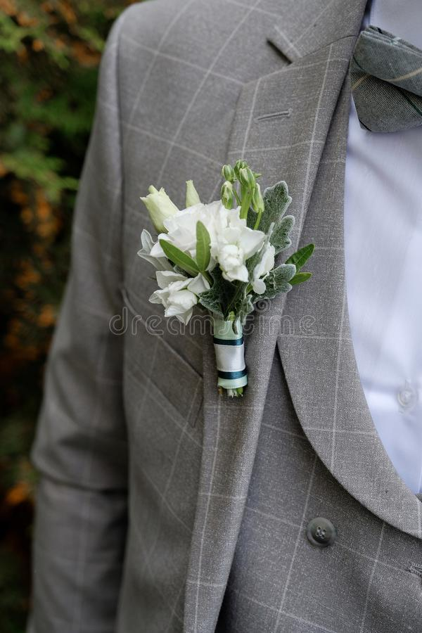 A young man or groom in a white shirt, a butterfly and a checkered gray vest or jacket. Beautiful boutonniere of white roses and royalty free stock photos
