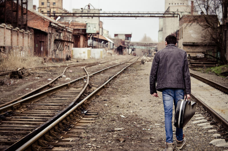 Young man with guitar case is going away royalty free stock photography