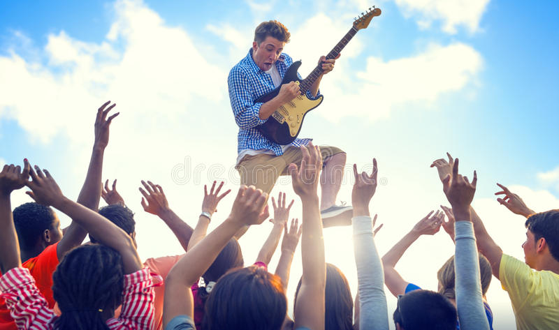 Young Man with a Guitar Performing on an Ecstatic Crowds stock photos