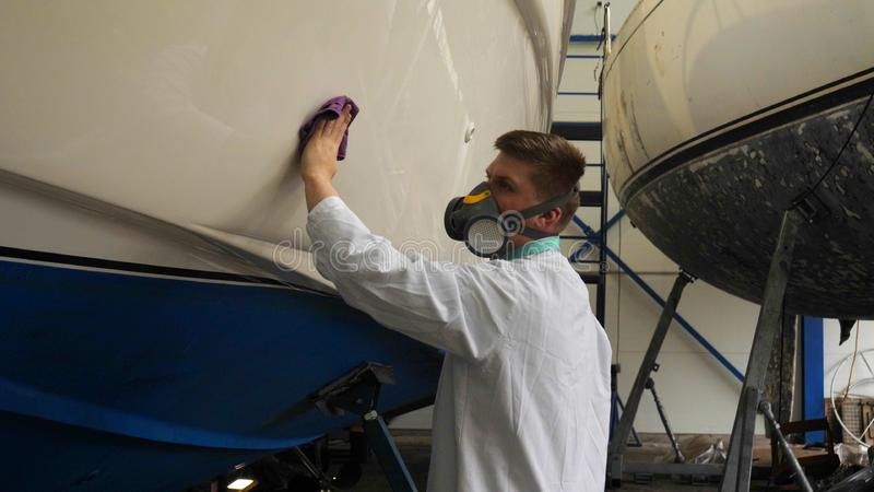 A young man guy is a specialist in cleaning the yacht, in a respirator and using a spray on the background of the yachts. Concep stock photo