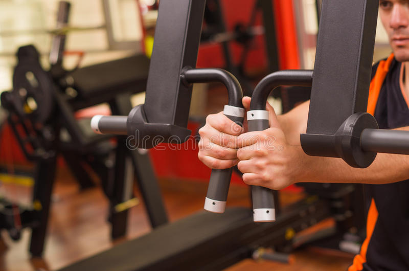 Young man in the gym and exercising Back on machine royalty free stock photography