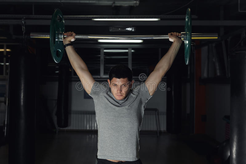 Young man at gym lifting a barbell. Young man at gym lifting a barbell royalty free stock photography