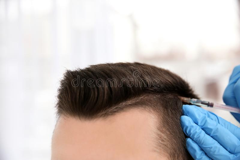 Young man with hair loss problem receiving injection. On blurred background, closeup royalty free stock photo