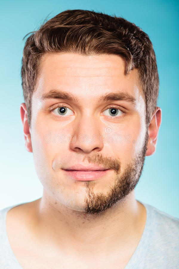 Young man with half shaved face beard hair. Portrait of young man with half shaved face beard hair. Handsome guy on blue. Skin care and hygiene stock photo