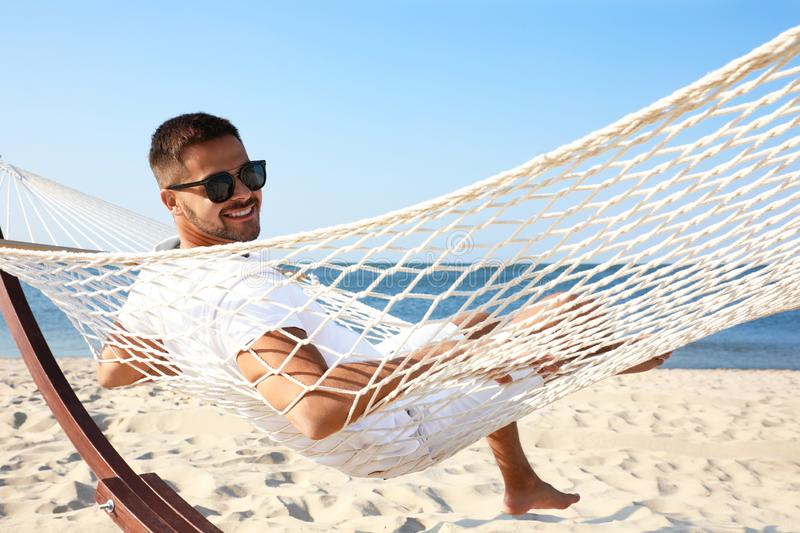Young man  in hammock on beach royalty free stock images