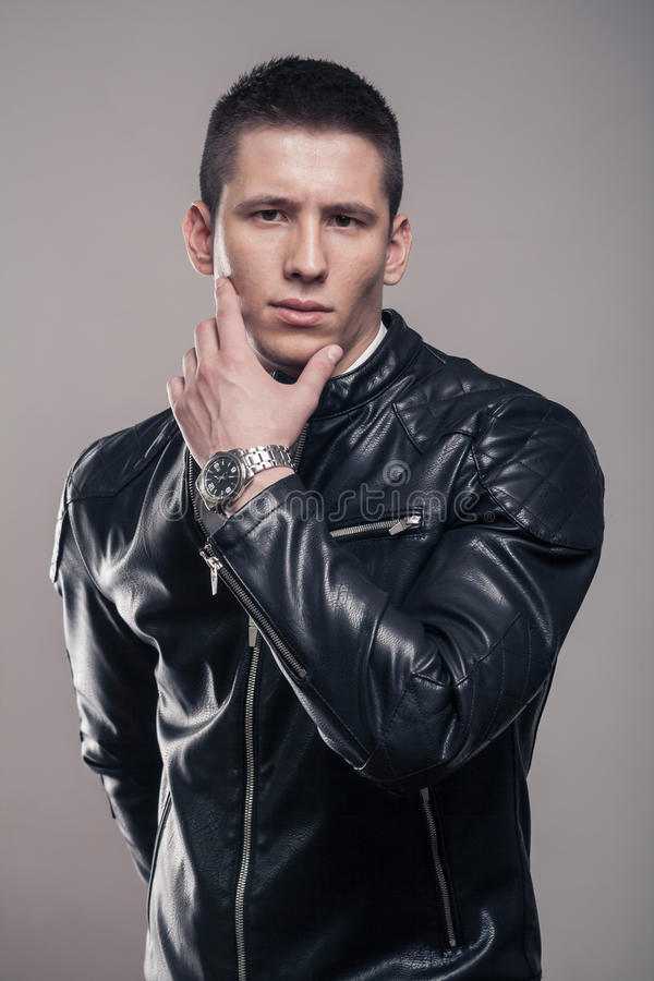 Young man, hand touching face, leather jacket, intense look. One young adult man only, hand touching face, looking tense, looking to the camera, leather jacket stock image