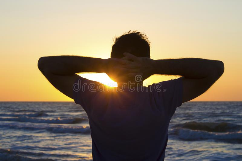 Young man hands behind head relax at sunrise sky sea royalty free stock photo