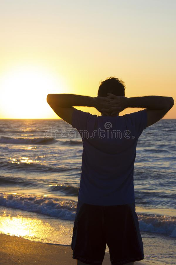 Young man hands behind head relax at sunrise sky sea royalty free stock photography