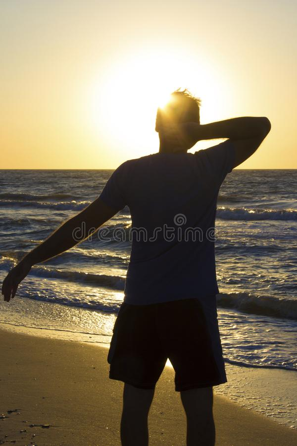 Young man hands behind head relax at sunrise sky sea. Young man hands behind head relax at sunrise on a background of blue sky and sea, horizon beach dawn royalty free stock photos