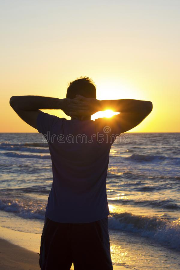 Young man hands behind head relax at sunrise sky sea stock photography
