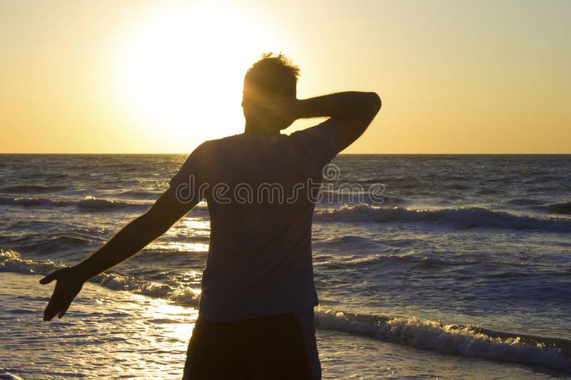 Young man hands behind head relax at sunrise sky sea royalty free stock photos