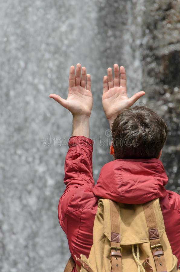 Young man with hands raised towards a waterfall of water. Country, castilla, leon, europe, mazobres, cascade, mountain, landscape, palencia, parque, natural stock image
