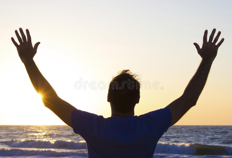 Young man hands up sunrise background blue sky and sea stock photos