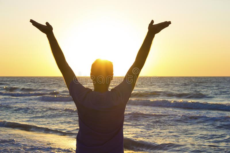 Young man hands up sunrise background blue sky and sea stock photo